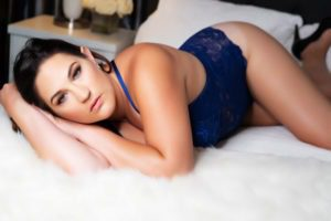 curvy woman posing on boudoir studio bed and white fur blanket