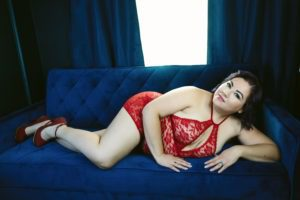 woman in red lingerie posing on boudoir studio couch