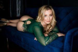 blonde woman posing in green lingerie bodysuit on blue boudoir studio couch