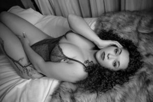 woman laying on her back on the boudoir studio bed