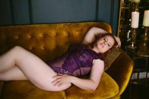 woman in purple bodysuit posing on gold boudoir studio couch
