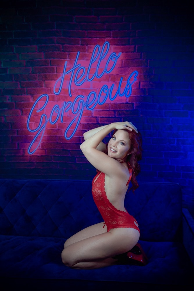 beautiful woman posing in front of society 6 hello gorgeous tapestry wearing red lacy bodysuit posing with her hands on her head and smiling