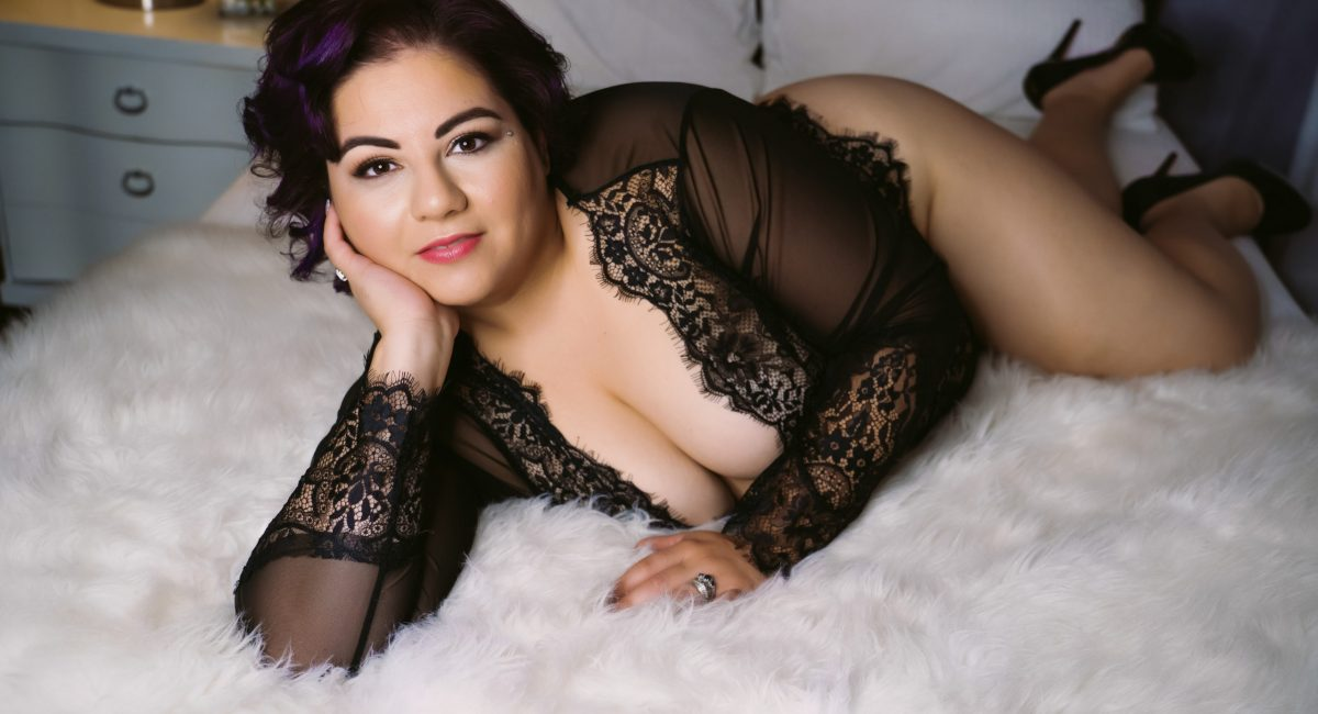 curvy woman with dark hair laying on bed in boudoir studio wearing long sleeved lace bodysuit